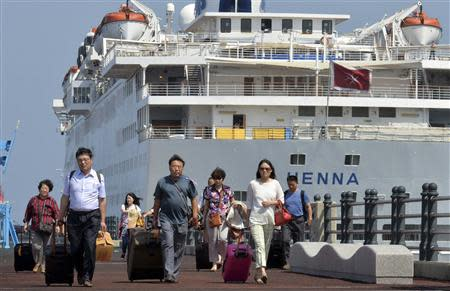 Passengers leave Chinese cruise ship Henna, which is stranded at the port of Jeju on Jeju island