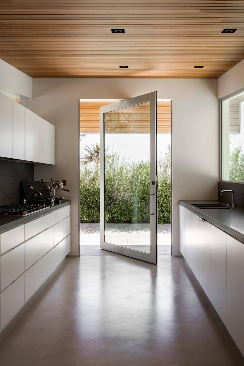 The kitchen features a large rotating door from Fleetwood, for easy access when entertaining outdoors. The coffee maker is from Slayer and the countertops were sourced from Basaltina.