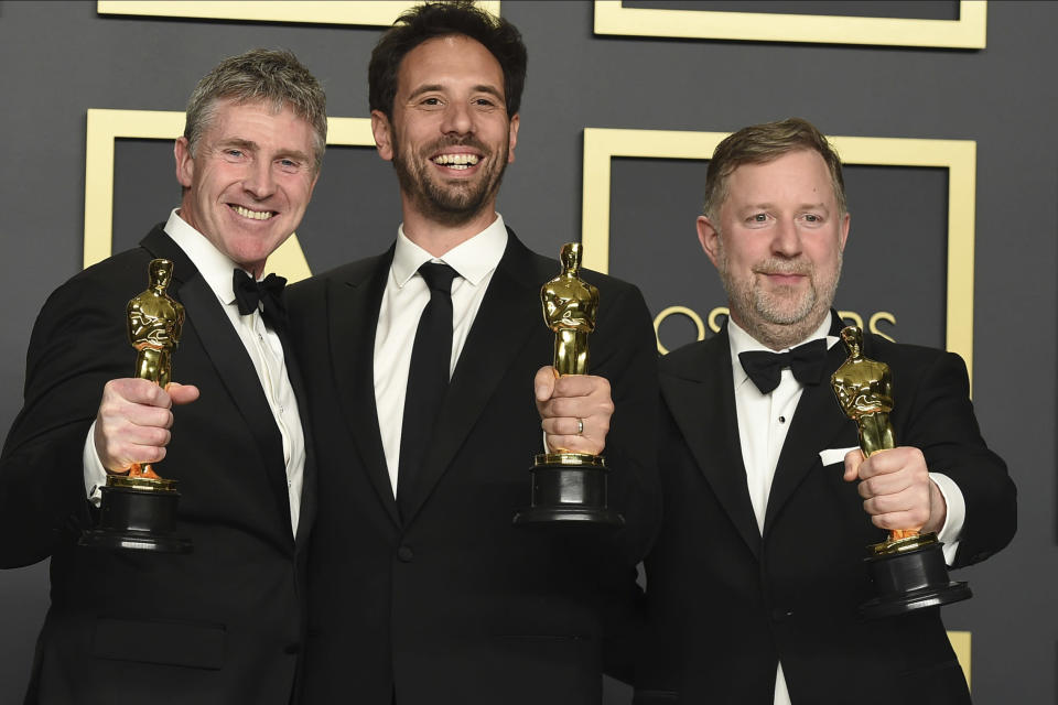 """Dominic Tuohy, from left, Guillaume Rocheron, and Greg Butler, winners of the award for best visual effects for """"1917"""", pose in the press room at the Oscars on Sunday, Feb. 9, 2020, at the Dolby Theatre in Los Angeles. (Photo by Jordan Strauss/Invision/AP)"""
