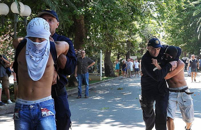 """Montenegro police officers arrest two men during the first ever pride event in the Montenegrin seaside resort of Budva, Wednesday, July 24, 2013. Dozens of extremists shouting """"Kill the gays"""" have attacked gay activists as they were gathering for the first ever pride event in staunchly conservative Montenegro. The assailants threw rocks, bottles and various other objects at some 20 gay activists and supporters and at special police securing the event in the coastal town of Budva on Wednesday. Police intervened to push the attackers away and the event continued as planned. (AP Photo/Risto Bozovic)"""