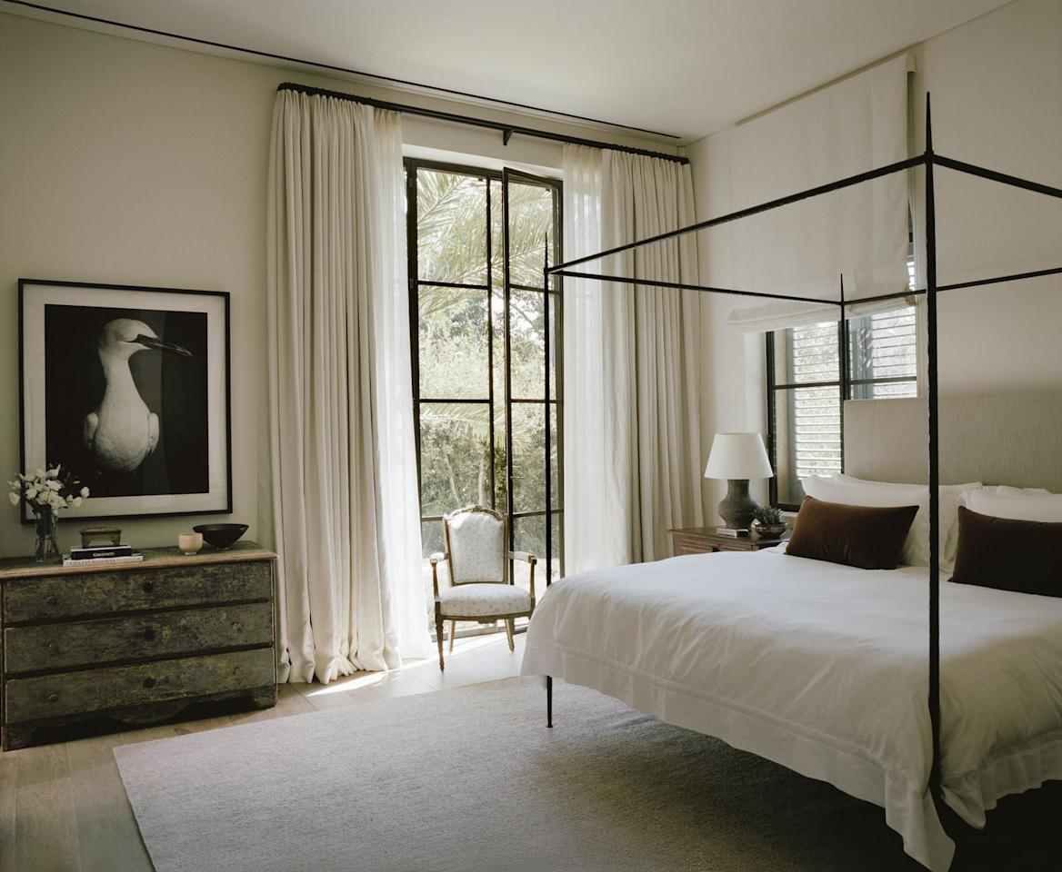 """<p>Near Tel Aviv, Israel, designer <a href=""""http://kevinspearman.com/"""" target=""""_blank"""">Kevin Spearman</a> celebrates the worldly charm of this Tuscan-style villa with a touch of American ease. The contemporary white furnishings and art of this guest bedroom energizes the traditional stone architecture. <a href=""""https://fave.co/2ITxbEa"""" target=""""_blank"""">Frette</a><br>linens dress the <a href=""""https://www.kerryjoyce.com/products"""" target=""""_blank"""">Kerry Joyce</a> iron bed with a <a href=""""https://fave.co/2PEn07g"""" target=""""_blank"""">Beauvais Carpets</a> rug beneath it. The armchair is Louis XVI. <br></p>"""