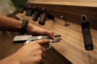 A seller demonstrates a gun inside the Big Boar gun shop in Brasilia, Brazil, Thursday, March 4, 2021. President Jair Bolsonaro signed four decrees that, among other things, will allow Brazilians to buy up to 8 guns, and carry two guns simultaneously – unless lawmakers vote down the measures. (AP Photo/Eraldo Peres)