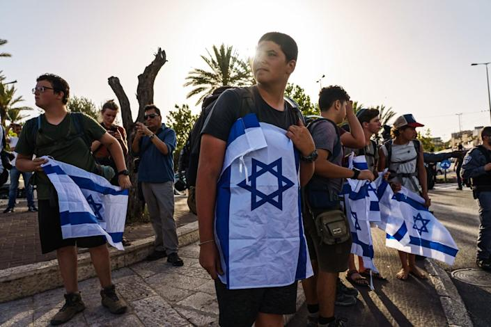 Young men stand in the street holding Israeli flags.