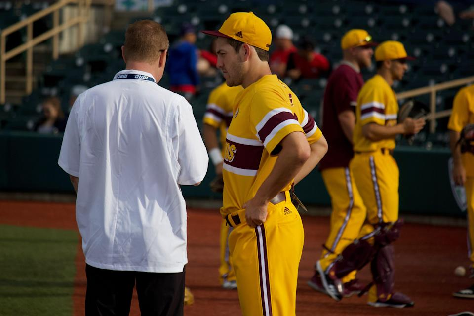 Central Michigan athletic director Mike Alford talks with infielder Zach Heeke at the MAC tournament on May 25, 2019, in Avon, Ohio.