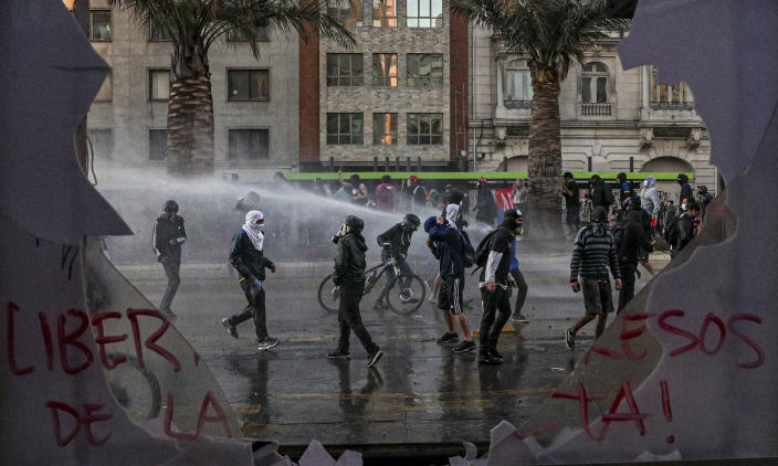 Anti-government protesters are sprayed by police with water during a protest against police in reaction to a video that appears to show an officer pushing a youth off a bridge the previous day at a protest, in Santiago, Chile, Saturday, Oct. 3, 2020. (AP Photo/Esteban Felix)