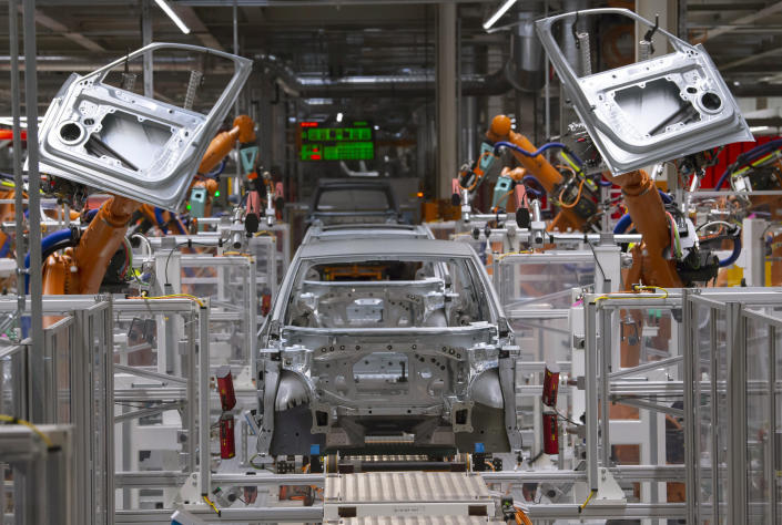 FILE- In this Tuesday, Feb. 25, 2020 file photo, robots work on an electric car ID.3 body at the assembly line during a press tour at the plant of the German manufacturer Volkswagen AG (VW) in Zwickau, Germany. The coronavirus has cancelled business plans all over the world but Europe's push into electric cars isn't one of them. Sales of battery-powered and hybrid cars have held up despite a deeply painful recession, mainly thanks to the action of governments. (AP Photo/Jens Meyer, file)