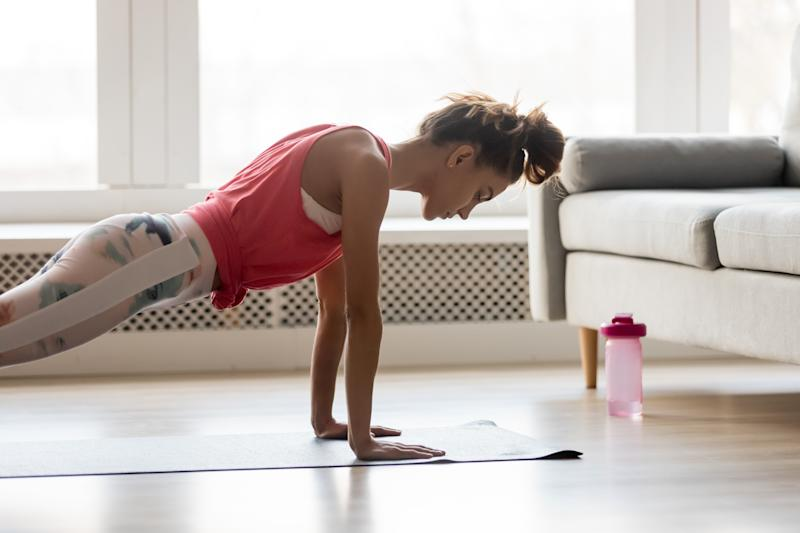 Young attractive sportive woman wearing activewear doing push ups or press ups exercise position on sport mat at home, practicing yoga plank pose, working out indoors, healthy active lifestyle concept
