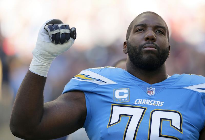 Los Angeles Chargers offensive tackle Russell Okung (76), raises his fist during the national anthem before an NFL football game against Tennessee Titans at Wembley stadium in London, Sunday, Oct. 21, 2018. (AP Photo/Tim Ireland)