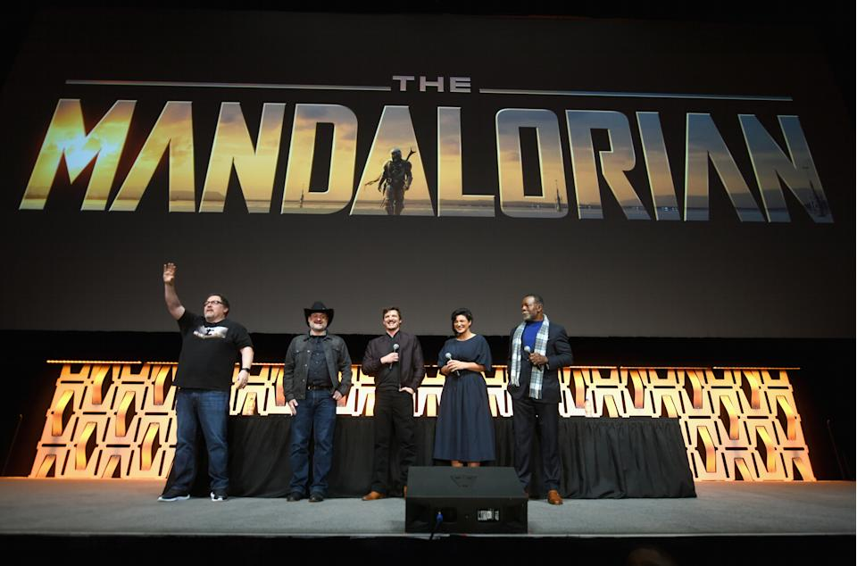 """CHICAGO, IL - APRIL 14:  (L-R) Writer/executive producer Jon Favreau, Director/executive producer Dave Filoni, Pedro Pascal (The Mandalorian), Gina Carano (Cara Dune) and Carl Weathers (Greef) onstage during """"The Mandalorian"""" panel at the Star Wars Celebration at McCormick Place Convention Center on April 14, 2019 in Chicago, Illinois.  (Photo by Daniel Boczarski/WireImage for Disney)"""