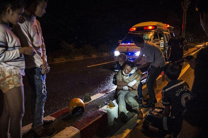 Vientiane Rescue volunteers help an injured motorcycle driver following a drink-driving accident in Laos (AFP Photo/Lillian Suwanrumpha)