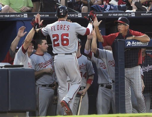 Washington Nationals' Jesus Flores is welcomed back to the dugout after his home run against the Atlanta Braves during the fourth inning of a baseball game, Friday, June 29, 2012, in Atlanta. (AP Photo/John Amis)