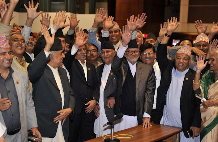 PM Sushil Koirala (3R),Unified Marxist Leninist chairman K P Oli (4R), Unified Communist Party of Nepal chairman Pushpa Kamal Dahal (4L) and other lawmakers wave as parliament passes a new national constitution in Kathmandu on September 16, 2015 (AFP Photo/Prakash Mathema)