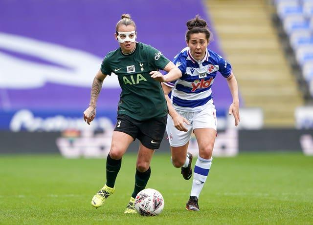 Tottenham's Ria Percival, left, sports a protective mask as she battles for possession with Reading's Fara Williams in the Women's Super League