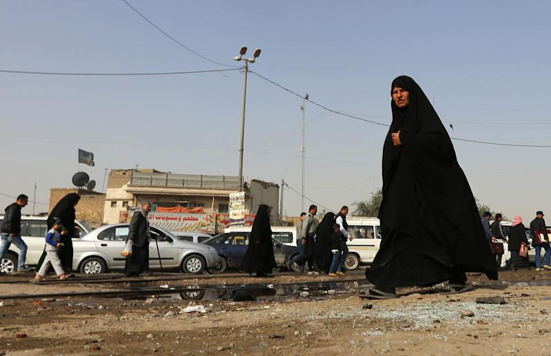 An Iraqi woman walks past a pool of blood on the aftermath of a suicide bomb attack in the Shiite-majority district of Kadhimiyah, north Baghdad, on February 9, 2015 (AFP Photo/Sabah Arar)