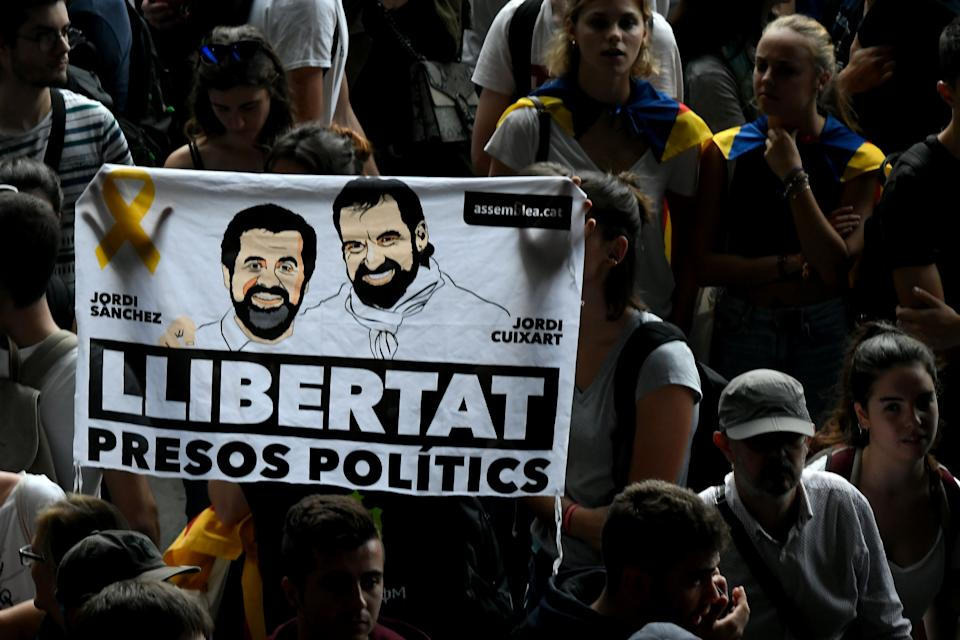 """Protesters hold a banner reading """"Free political prisoners"""" at El Prat airport in Barcelona on October 14, 2019 as thousands took to the streets after Spain's Supreme Court sentenced nine Catalan separatist leaders to between nine and 13 years in jail for sedition over the failed 2017 independence bid. - As the news broke, demonstrators turned out en masse, blocking streets in Barcelona and elsewhere as police braced for what activists said would be a mass response of civil disobedience. (Photo by LLUIS GENE / AFP) (Photo by LLUIS GENE/AFP via Getty Images)"""