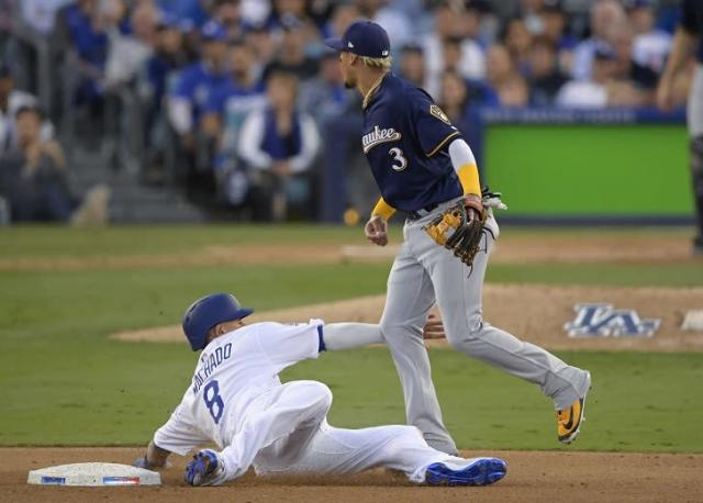 Dodgers runner Manny Machado is called out for interference after making unnecessary contact with Brewers shortstop Orlando Arcia. (AP)