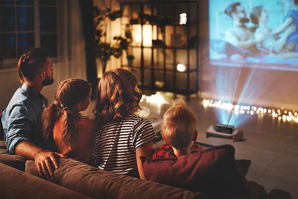 a young man, a girl in pigtails, a woman with short hair, and a young boy sit on a couch and look at family vacation photos projected onto their living room wall