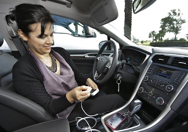 """In this Tuesday, Dec. 18, 2012, photo, Gigi Swanson, Digital Alliances and Partnerships Strategist for Cox Target Media Inc., owner of Valpak, checks coupons through the phone application """"Roximity"""" and Ford's SYNC,  in St. Petersburg, Fla. Valpak has partnered with Roximity, a Denver-based app developer, to bring coupons and deals to drivers of newer-model Fords and Lincolns who use the voice-controlled Sync AppLink connected to their mobile phone. (AP Photo/Chris O'Meara)"""