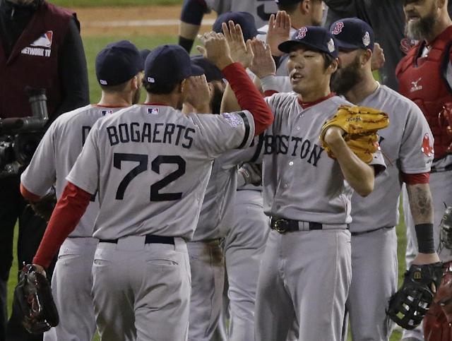 Boston Red Sox relief pitcher Koji Uehara (19) and Xander Bogaerts (72) celebrate after Boston defeated the St. Louis Cardinals in Game 5 of baseball's World Series Monday, Oct. 28, 2013, in St. Louis. The Red Sox won 3-1 to take a 3-2 lead in the series. (AP Photo/Charlie Riedel)