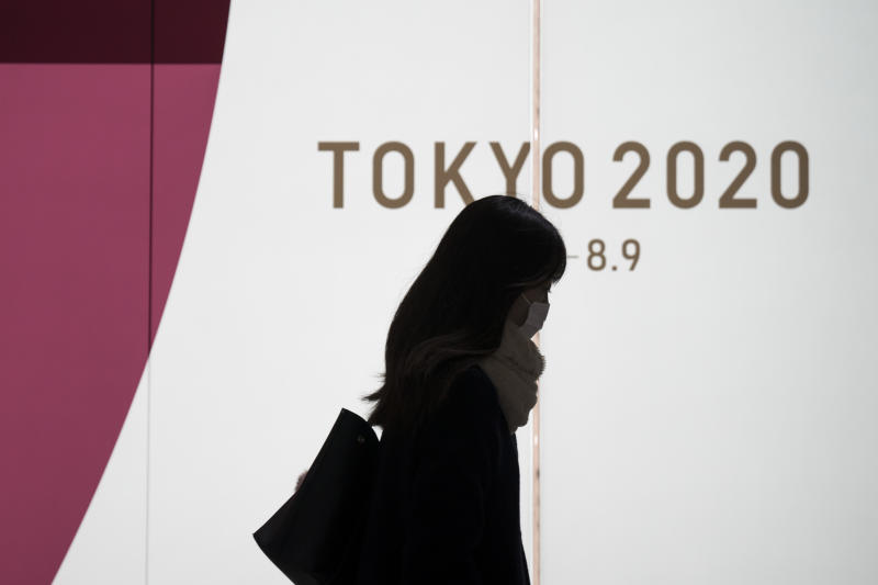 TOKYO, JAPAN - FEBRUARY 26: A pedestrian wearing a face mask walks past a display promoting the upcoming Tokyo 2020 Olympic and Paralympic Games on February 26, 2020 in Tokyo, Japan. Concerns that the Tokyo Olympics may be postponed or cancelled are increasing as Japan confirms 862 cases of Coronavirus (COVID-19) and as some professional sporting contests are being called off or rescheduled and some major Japanese corporations ask for people to work from home. (Photo by Tomohiro Ohsumi/Getty Images)