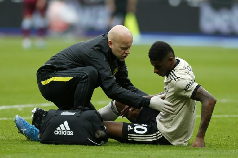 Manchester United striker Marcus Rashford receives medical attention during the Premier League match against West Ham