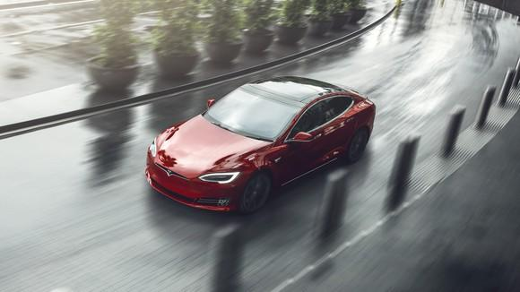 Red Model S driving on a curved road