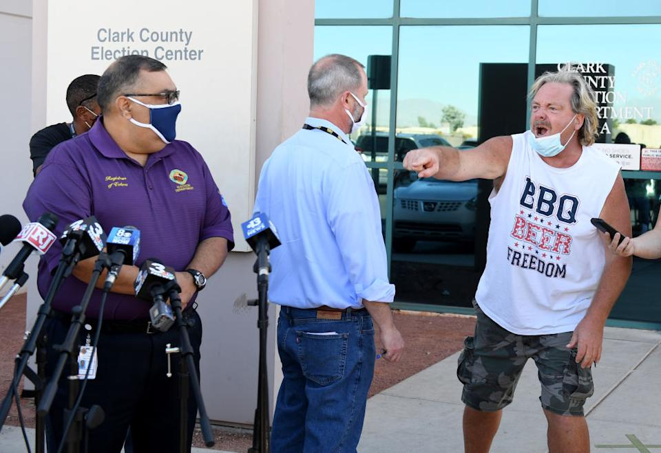Clark County public information officer Dan Kulin steps in front of a protester (R) as he interrupts a news conference to discuss ballot counting by Clark County Registrar Joe Gloriaat the Clark County Election Department in North Las Vegas, Nevada. US.