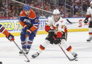 Calgary Flames' Sean Monahan (23) is chased by Edmonton Oilers' Milan Lucic (27) during first period NHL hockey action in Edmonton, Alberta on Sunday, Dec. 9, 2018. (Jason Franson/The Canadian Press via AP)