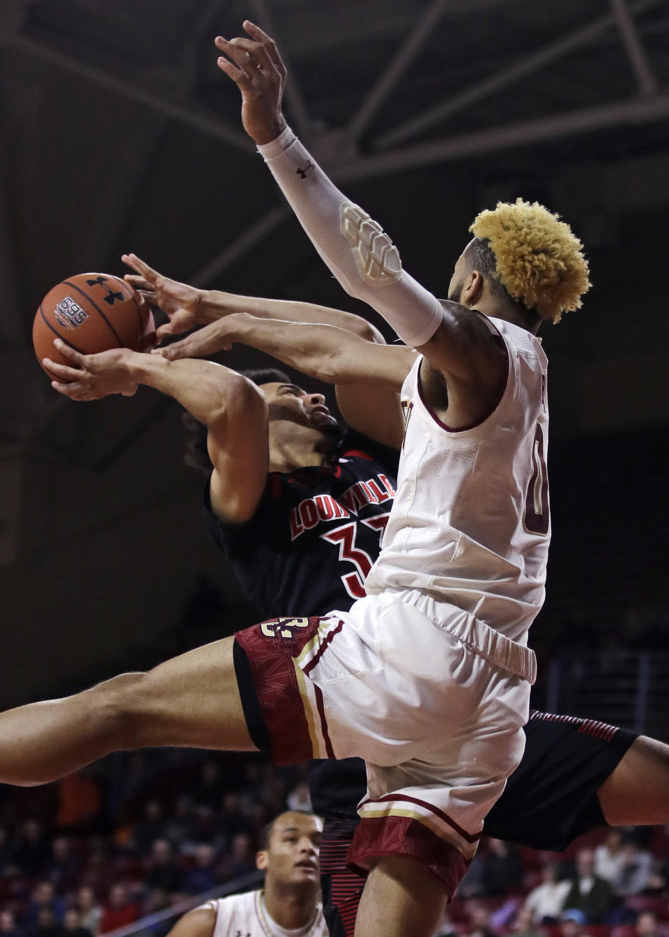 Boston College guard Ky Bowman, right, blocks a shot by Louisville forward Jordan Nwora, left, during the first half of an NCAA college basketball game in Boston, Wednesday, Feb. 27, 2019. (AP Photo/Charles Krupa)