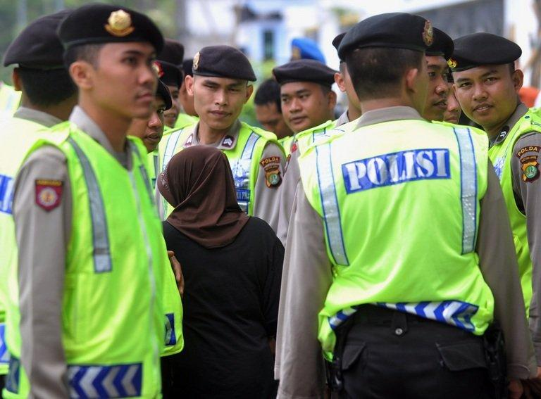 An Indonesian woman walks past Indonesian policemen in Jakarta on February 20, 2012