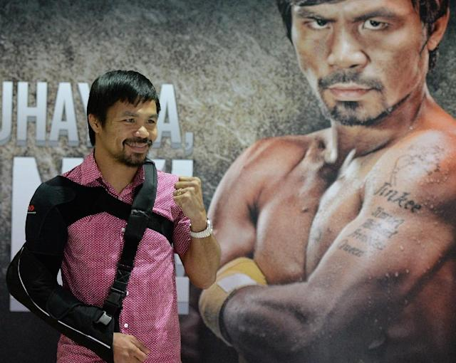 Filipino boxer Manny Pacquiao is pictured on May 13, 2015 with his arm in a sling shortly after arriving from the US at the international airport in Manila (AFP Photo/Ted Aljibe)