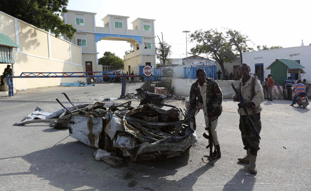 Somali government soldiers stand near the wreckage of a car destroyed during an attack at the presidential palace in the capital Mogadishu July 9, 2014. Islamist militants attacked Somalia's presidential compound on Tuesday with a car bomb and gunmen broke through a perimeter wall but were repulsed by security forces, and the president was not there at the time, the interior ministry said. REUTERS/Feisal Omar (SOMALIA - Tags: MILITARY CIVIL UNREST POLITICS CRIME LAW)