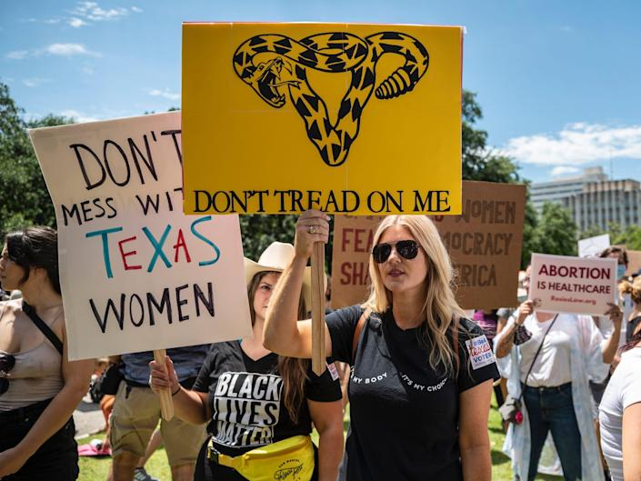 Protesters hold up signs at a protest against Texas' new abortion law outside the state capitol on May 29, 2021 in Austin, Texas.