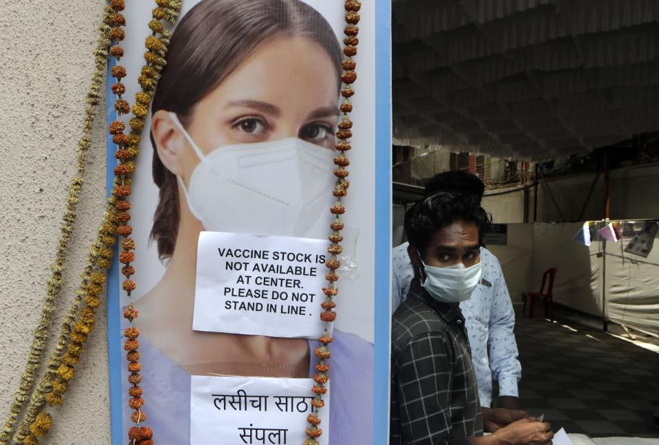 A volunteer waits outside a vaccination center which has been closed because of shortage of the COVID-19 vaccine in Mumbai, India, Friday, April 9, 2021. India has a seven-day rolling average of more than 100,000 cases per day and has reported 13 million virus cases since the pandemic began, the third-highest total after the United States and Brazil. (AP Photo/Rajanish Kakade)