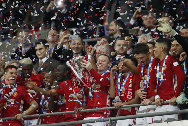 FILE - In this file photo dated Sunday, Feb. 26, 2017, United's Wayne Rooney lifts the trophy after they won the English League Cup final soccer match between Manchester United and Southampton FC at Wembley stadium in London. It is announced Tuesday Aug. 6, 2019, that 33-year old former England captain Wayne Rooney will be leaving US Major League Soccer team D.C. United to join second-tier English Championship team Derby County as player-coach from January 2020. (AP Photo/Kirsty Wigglesworth, FILE)