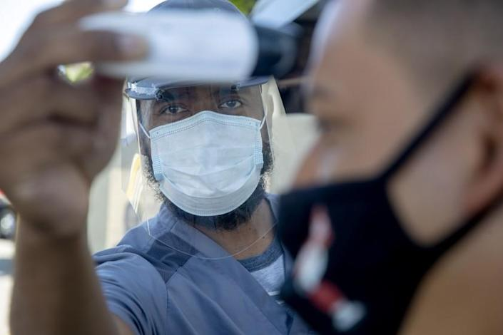 MISSION HILLS, CA - JULY 10: Nurse Bobby Binissa, left, takes temperature of patient Felix Camacho, of San Fernando, who may be showing symptoms of COVID-19 at Providence Holy Cross Medical Center on Friday, July 10, 2020 in Mission Hills, CA. (Brian van der Brug / Los Angeles Times)