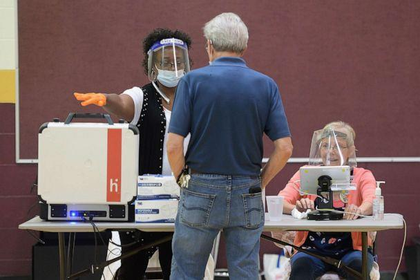 PHOTO: A poll worker helps a voter access his ballot at Keevan Elementary School, Aug. 4, 2020, in St. Louis. (Michael B. Thomas/Getty Images)