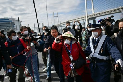 A passenger (C) from the stricken Diamond Princess leaves after a controversial 14-day quarantine on board the ship in Japan's port of Yokohama