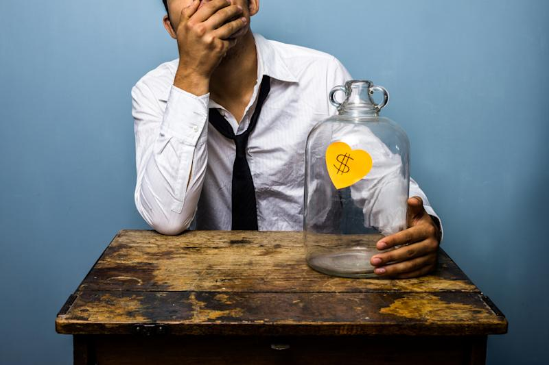 A man is sitting at a small desk with his face in his palm, holding an empty jar with a dollar sign on it.
