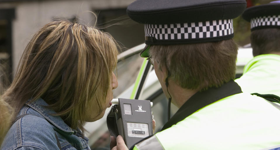 A stock image of a policeman breathalysing a woman.