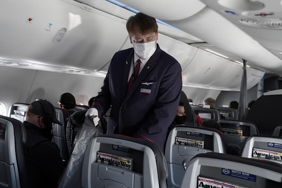 A flight attendant gathers trash on a media flight aboard a Boeing 737 Max airplane from Dallas Fort Worth Airport to Tulsa, Oklahoma in Dallas, Texas, U.S., December 2, 2020. REUTERS/Carlo Allegri