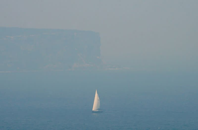 A sailing boat is seen through smoke haze from bushfires in front of the cliffs of North Head, Sydney Harbour