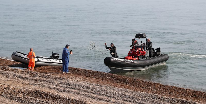 Border Force staff recover an inflatable boat at Kingsdown beach, near Dover, Kent, where it was abandoned by people thought to be migrants who had used it to cross the English Channel.