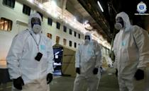 Police officers in protective gear prepare to board the coronavirus-stricken Ruby Princess cruise ship and seize its black box at Port Kembla, Australia