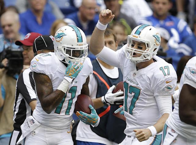 Miami Dolphins' Ryan Tannehill (17) celebrates with Mike Wallace (11) after Wallace scored on an 18-yard touchdown reception during the first half an NFL football game against the Indianapolis Colts Sunday, Sept. 15, 2013, in Indianapolis. (AP Photo/Michael Conroy)