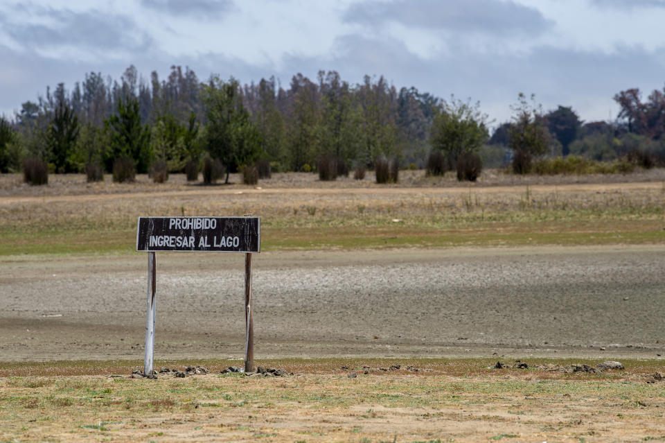 A sign sits in the middle of a barren field in Chile.