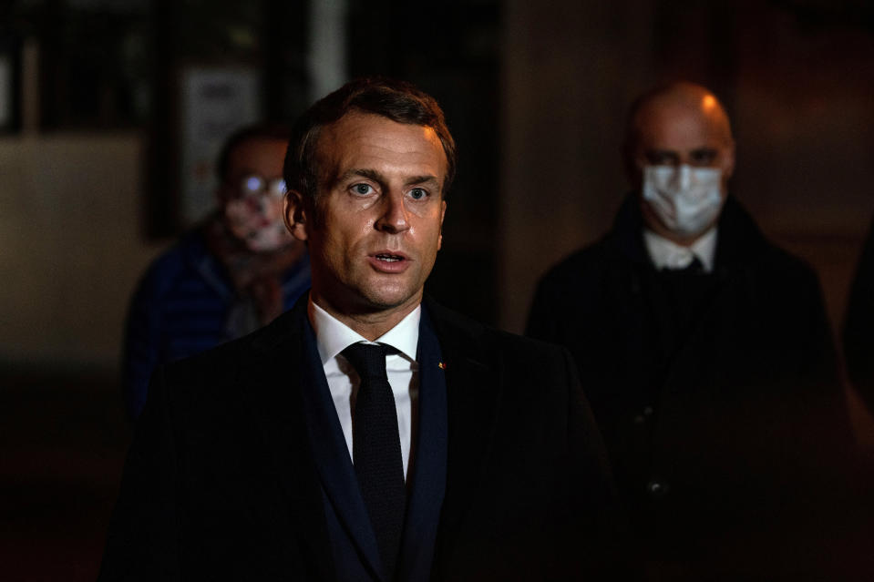 """French President Emmanuel Macron speaks in front of a high school Friday Oct.16, 2020 in Conflans Sainte-Honorine, northwest of Paris, where a history teacher who opened a discussion with high school students on caricatures of Islam's Prophet Muhammad was beheaded. French President Emmanuel Macron denounced what he called an """"Islamist terrorist attack"""" against a history teacher decapitated in a Paris suburb Friday, urging the nation to stand united against extremism. (Abdulmonam Eassa, Pool via AP)"""