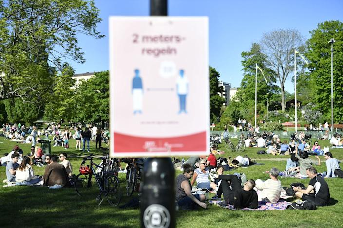 eople enjoy the sunny weather in Tantolunden park near a sign about social distancing in Stockholm in May 2020, amid the novel coronavirus pandemic.
