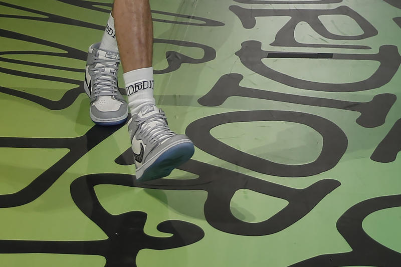 In this Tuesday, Dec. 3, 2019, photo, a model walks the runway wearing the Christian Dior pre-fall 2020 men's fashion collection shoe Air Dior during Miami Art Week on, in Miami. (AP Photo/Brynn Anderson)