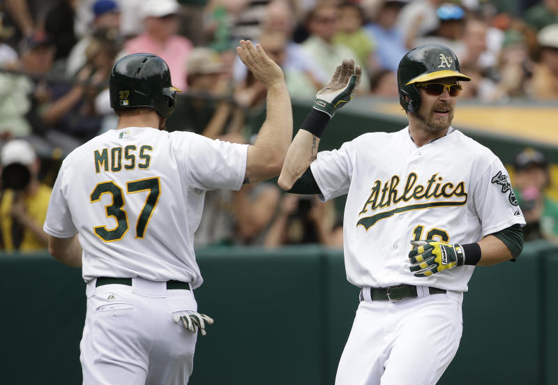 Oakland Athletics' Josh Reddick, right, is greeted by teammate Brandon Moss, left, after scoring in the fourth inning of their interleague baseball game against the New York Mets Wednesday, Aug. 20, 2014, in Oakland, Calif. Both Reddick and Moss scored after the Athletics' Andy Parrino reached on a fielding error by Mets second baseman Daniel Murphy. (AP Photo/Eric Risberg)